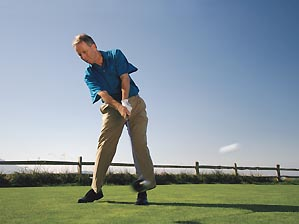 a golfer topping the golf ball